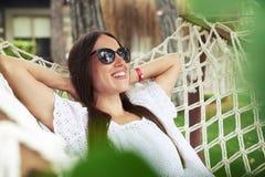 Plan rapproché de jeune femme attirante dans des lunettes de soleil se situant dans le hammoc Image libre de droits