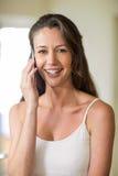 Plan rapproché de jeune femme parlant au téléphone portable Images stock