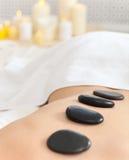 Plan rapproché de jeune femme recevant le massage en pierre chaud Image stock