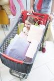 Plan rapproché de jeune fille dans le chariot poussé par le père et la mère Images libres de droits