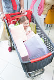 Plan rapproché de jeune fille dans le chariot poussé par le père et la mère Photographie stock libre de droits