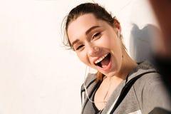 Plan rapproché de jeune jolie femme heureuse de sport, regardant des WI d'appareil-photo Photos stock