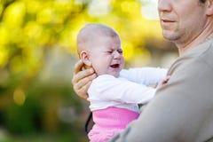 Plan rapproché de jeune père fatigué avec le bébé pleurant Photo stock