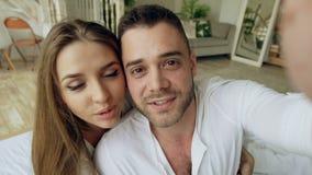 Plan rapproché de jeunes couples mignons et affectueux ayant la causerie visuelle tenant le smartphone et causant aux amis s'asse banque de vidéos