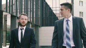 Plan rapproché de jeunes hommes d'affaires marchant sur le fond de centre d'affaires banque de vidéos