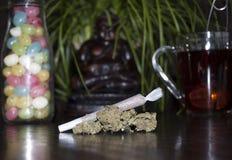 Plan rapproché de joint et de bourgeons roulés de mauvaise herbe de marijuana, sur le fond en bois Photo libre de droits