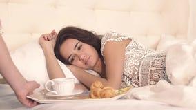 Plan rapproché de jolie jeune femme de sommeil dans le lit se réveillant par le petit déjeuner dans le lit clips vidéos