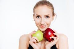 Plan rapproché de jolie sportive de sourire avec les pommes vertes et rouges Photos libres de droits