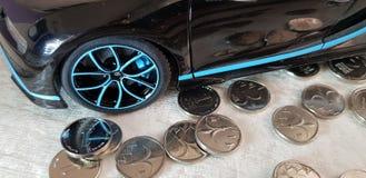 Plan rapproché de jouet noir en métal de Bugatti Chiron avec les roues bleues se tenant sur le groupe de pièces de monnaie israél photo libre de droits