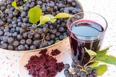 Plan rapproché de jus et de confiture frais de melanocarpa noir mûr d'Aronia de chokeberry dans le verre et la baie dans le pot s Photographie stock libre de droits