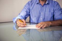 Plan rapproché de l'écriture de l'homme sur un morceau de papier Images libres de droits