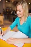Plan rapproché de l'écriture heureuse de jeune femme sur le livre images stock