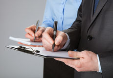 Plan rapproché de l'équipe travaillante d'affaires prenant des notes Photographie stock libre de droits