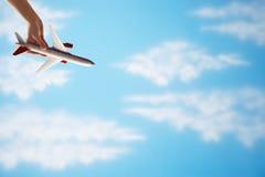 Plan rapproché de l'avion de jouet de vol de la main de la femme à l'envers contre le ciel nuageux Images stock