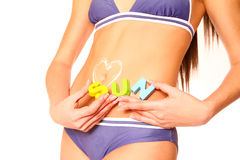 Plan rapproché de l'estomac de la femme avec le coeur de lotion du soleil et soleil de mot sur W Images stock
