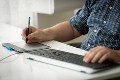 Plan rapproché de l'homme à l'aide du comprimé graphique numérique et du clavier à l'offi Photographie stock libre de droits