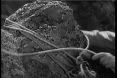 Plan rapproché de l'homme attachant la corde autour de la roche banque de vidéos