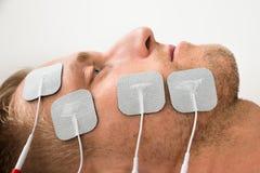 Plan rapproché de l'homme avec des électrodes sur le visage Image stock