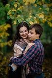 Plan rapproché de l'homme avec la femme riant et étreignant dans la forêt en automne photos stock