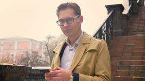 Plan rapproché de l'homme caucasien attirant dactylographiant sur la vue de rotation de téléphone à la caméra et la position de s banque de vidéos