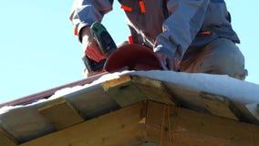 Plan rapproché de l'homme dans des vêtements de travail avec la perceuse électrique installant la tuile rouge en métal sur la mai clips vidéos