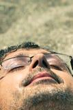 Plan rapproché de l'homme dormant sur la plage Photographie stock libre de droits