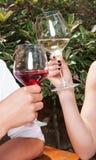 Plan rapproché de l'homme et de la femme grillant des verres de vin Photographie stock