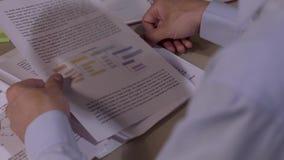 Plan rapproché de l'homme regardant par quelques documents banque de vidéos