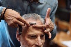 Plan rapproché de l'homme supérieur ayant la coupe de cheveux au raseur-coiffeur Photographie stock