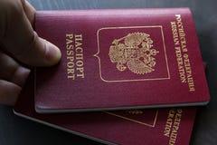 Plan rapproché de l'homme tenant deux passeports rouges sur le contrôle de passeport concept de course Images stock
