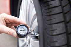 Plan rapproché de l'homme vérifiant la pression de pneu de voiture avec la mesure Images libres de droits