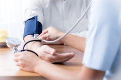Plan rapproché de l'infirmière avec le stéthoscope vérifiant la tension artérielle du Se Images stock