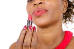 Plan rapproché de la belle femme africaine regardant son rouge à lèvres Images stock