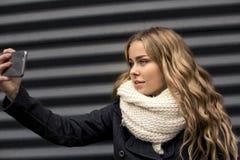 Plan rapproché de la belle jeune femme caucasienne blonde heureuse prenant un selfie sur le smartphone dehors en parc en automne Photos stock