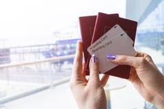 Plan rapproché de la belle main de femme tenant des passeports et des billets de carte d'embarquement sur le terminal d'aéroport  Photo libre de droits
