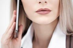 Plan rapproché de la bouche et lèvres d'une femme parlant sur un smartphone sur un fond blanc photographie stock