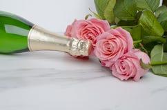 Plan rapproché de la bouteille de vin, belles roses sur le fond blanc Jour du `s de Valentine images stock