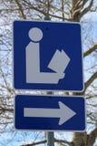 Plan rapproché de la direction au signe de bibliothèque avec l'arbre à l'arrière-plan Photos stock