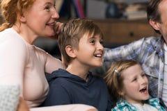 Plan rapproché de la famille de sourire heureuse s'asseyant sur le divan regardant TV, parents passant le temps avec des enfants Images libres de droits