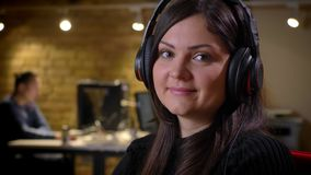 Plan rapproché de la femme d'affaires heureuse caucasienne adulte dans des écouteurs regardant l'american national standard de ca banque de vidéos