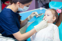 Plan rapproché de la fille assez petite ouvrant le sien bouche au loin pendant l'inspection de la cavité buccale au dentiste Photo libre de droits