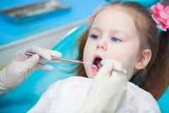 Plan rapproché de la fille assez petite ouvrant le sien bouche au loin pendant l'inspection de la cavité buccale au dentiste Photographie stock