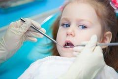Plan rapproché de la fille assez petite ouvrant le sien bouche au loin pendant l'inspection de la cavité buccale au dentiste Photos libres de droits