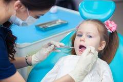 Plan rapproché de la fille assez petite ouvrant le sien bouche au loin pendant l'inspection de la cavité buccale au dentiste Photo stock
