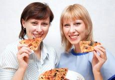 Plan rapproché de la fille et de la femme mangeant de la pizza. Photographie stock libre de droits
