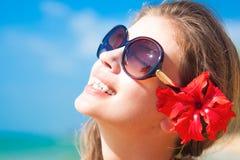 Plan rapproché de la jeune femme dans des lunettes de soleil souriant dessus Image stock