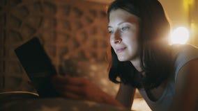 Plan rapproché de la jeune jolie femme à l'aide de la tablette à la nuit se trouvant dans le lit à la maison image libre de droits