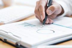 Plan rapproché de la lecture et de l'écriture d'homme d'affaires de mains avec le contrat de signature de stylo au-dessus du docu photos stock