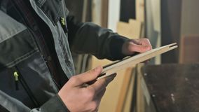 Plan rapproché de la main d'un charpentier masculin vérifiant la douceur et l'aptitude d'une planche en bois après traitement banque de vidéos