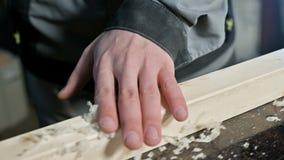 Plan rapproché de la main d'un charpentier masculin vérifiant la douceur et l'aptitude d'une planche en bois après traitement clips vidéos